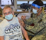 Older man wearing a Navy T-shirt gets a shot in his left arm from a guy wearing a Navy camo uniform.