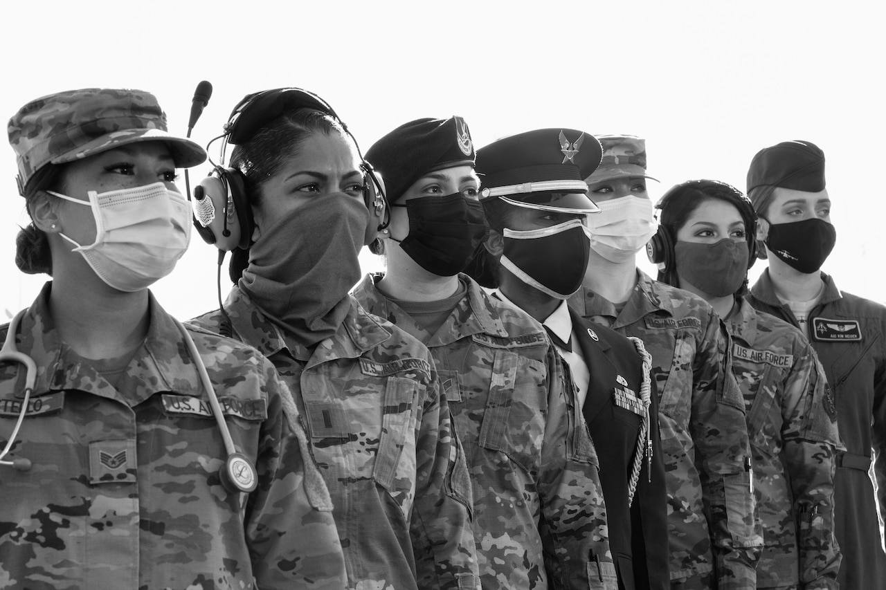 Women in uniform who hold a range of jobs in the Air Force stand in line.