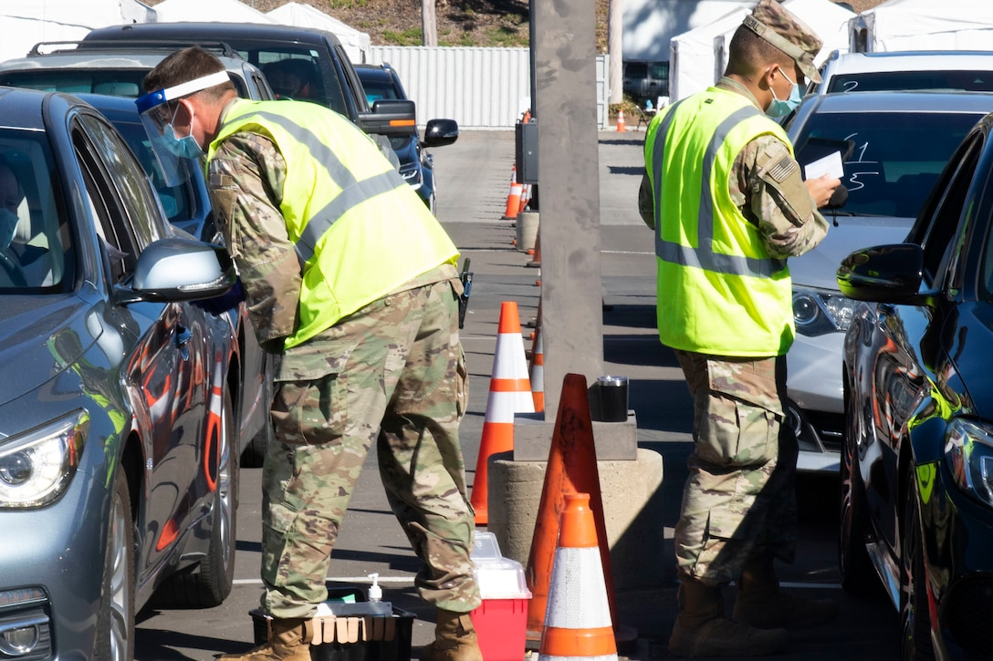 Two soldiers speak with Californians getting a vaccine in a drive-up facility.