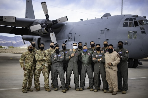 """Members of the 41st Electronic Combat Squadron """"Black Heritage Flight"""" pose for a photo in front of an EC-130 Compass Call at Davis-Monthan Air Force Base, Arizona on Feb. 17, 2021."""