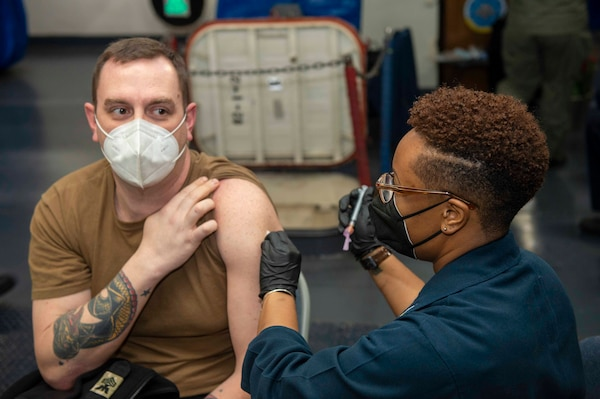 Sonar Technician 1st Class Brian Sims receives a second dose of the COVID-19 vaccination from Hospital Corpsman 1st Class Autumn Nichols aboard the USS Dwight D. Eisenhower (CVN 69).