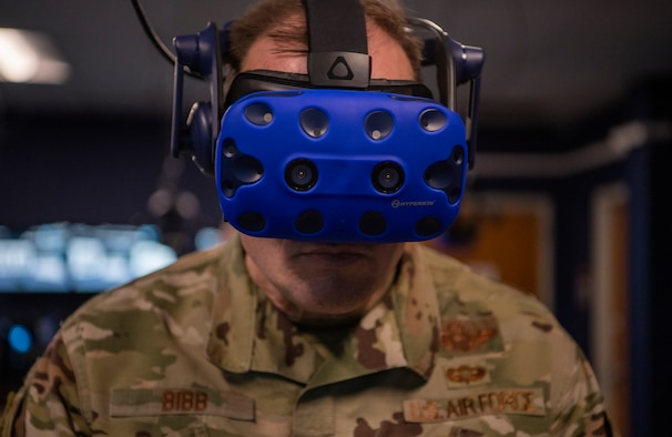 Chief Master Sgt. Chad Bickley, 18th Air Force command chief, right, and Maj. Gen. Thad Bibb, 18th AF commander, left, speak with Maj. Lacey Koelling, 317th Maintenance Group maintenance operation flight commander, about the virtual reality lab at Dyess Air Force Base, Texas, Mar. 3, 2021.
