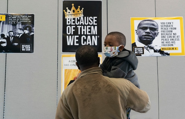 An airman holds his young son while reading a poster.