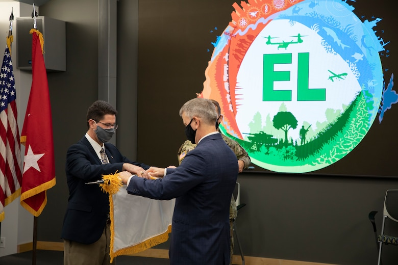 Dr. Edmond Russo, left, director of the U.S. Army Engineer Research and Development Center's (ERDC) Environmental Laboratory (EL), unfurls the Senior Executive Service (SES) flag with ERDC Director Dr. David Pittman during a hybrid virtual and in-person SES induction ceremony held at the ERDC-EL building in Vicksburg, Miss., March 11, 2021.