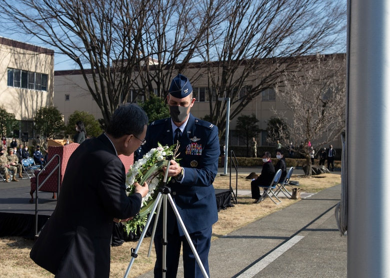 Col. Andrew Campbell, 374th Airlift Wing commander, and Takahisa Matsuda, North Kanto Defense Bureau director general place a wreath at the base of a Japanese flagpole during a ceremony for the 10th Anniversary of the Great East Japan Earthquake and the Operation Tomodachi support efforts at Yokota Air Base, Japan, March 11, 2021. The wreath represents the loss of nearly 16,000 lives during the earthquake, and the tsunami that followed. (U.S. Air Force photo by Staff Sgt. Joshua Edwards)