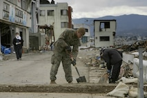 震災当時8歳だった菊田航さんが、宮城県気仙沼大島の実家の瓦礫をかき分けて貴重品を見つけようとしていた2011年4月3日の写真