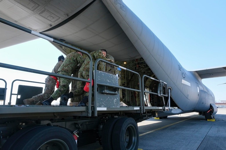374th Logistics Readiness Squadron Combat Mobility Flight Airmen and Japan Ground Self-Defense Force personnel load JGSDF container delivery system bundles onto a C-130J Super Hercules for an equipment airdrop as part of exercise Airborne 21