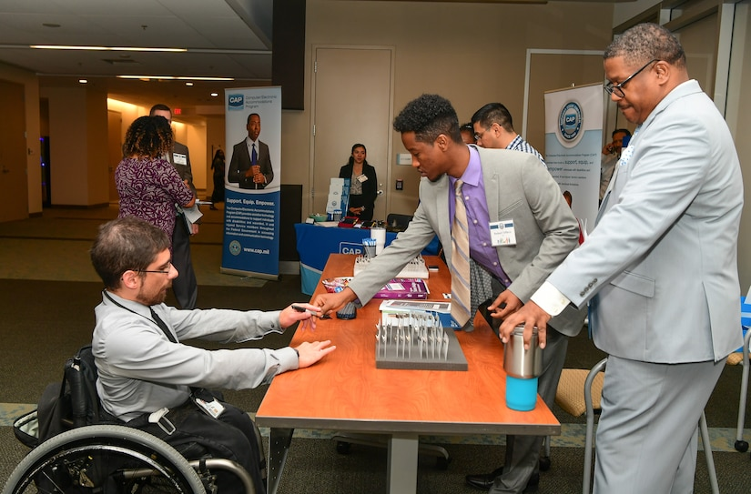 A man behind a display desk hands a man in a wheelchair a pen-like device.