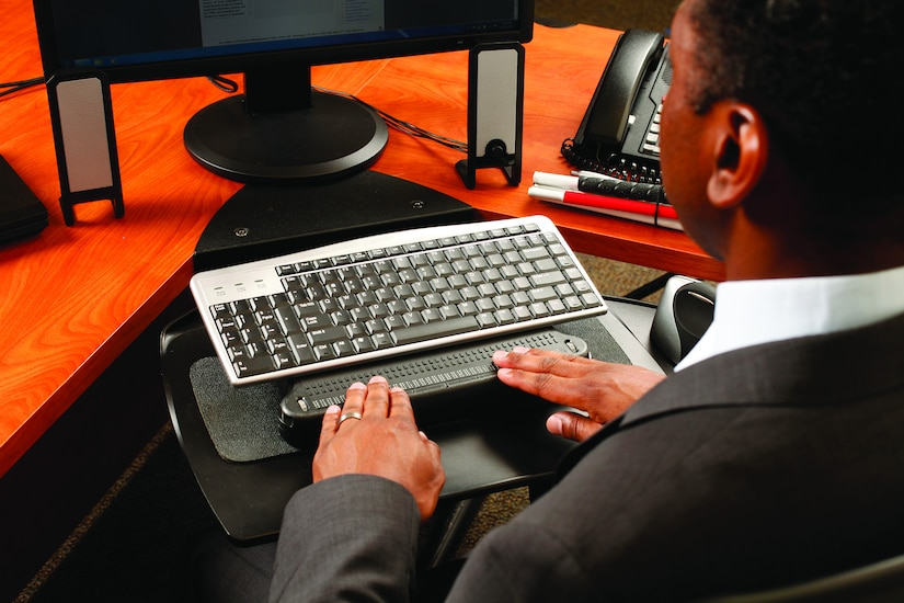 A man holds his hands over a keyboard attachment that allows him to read Braille.