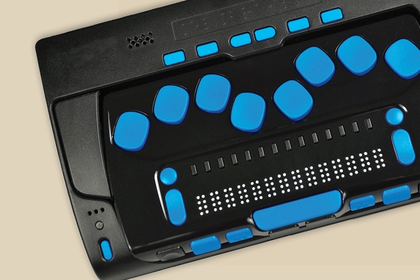 A special keyboard has several blue buttons and a line of Braille.