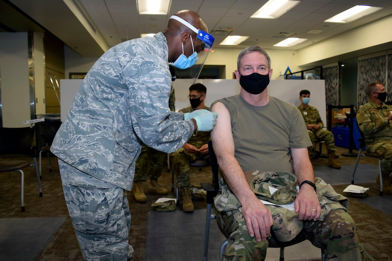 Capt. Albert Scott Jr., 433rd Medical Squadron critical care nurse, administers a COVID-19 vaccine to Col. Terry W. McClain, 433rd Airlift Wing commander, at Joint Base San Antonio-Lackland, Texas March 6, 2021. McClain was in the first group of members to receive the vaccine. (U.S. Air Force photo by Senior Airman Brittany Wich)