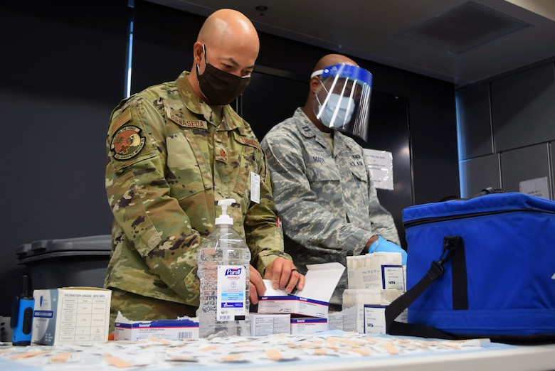Maj. Jerry Buenaseda, 433rd Aerospace Medicine Squadron clinical nurse, and Capt. Albert Scott Jr., 433rd Medical Squadron critical care nurse, prepare to distribute the COVID-19 vaccine to 433rd Airlift Wing members at Joint Base San Antonio-Lackland, Texas March 7, 2021. The COVID-19 vaccination rollout took a year in planning, strategizing, and training personnel. (U.S. Air Force photo by Tech Sgt. Mike Lahrman)
