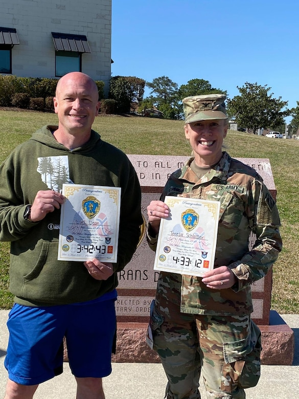 U.S. Army Engineer Research and Development Center Commander Col. Teresa Schlosser and Maj Earl Dean hold certificates recognizing their exceptional completion times during the 18.6-mile Norwegian Foot March at Camp Shelby Joint Forces Training Center, near Hattiesburg, Miss., March 6, 2021. Schlosser, Dean and four additional ERDC Soldiers, including Lt. Col. Christian Patterson, British Liaison Maj. Peter Mackintosh, Capt. Patrick Border and Capt. Jeremiah Paterson, completed the event. (U.S. Army Corps of Engineers photo)
