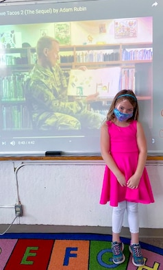 Savannah Preston, a Holloman Elementary School student, poses in front of a video of her father, Col. Thomas Preston, 49th Maintenance Group commander, reading for Read Across America March 10, 2021, on Holloman Air Force Base. Leaders of the community volunteered to read books to the students to help celebrate Read Across America. (Courtesy photo)