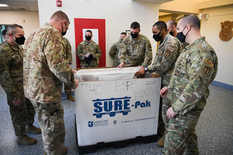 Members of the 66th Security Forces Squadron unpack memorials for Senior Airmen Kcey Ruiz and Nathan Sartain at Hanscom Air Force Base, Mass., March 10.