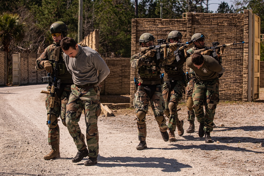 Dutch Marines with 32nd Raiding Squadron escort notional enemy prisoners during a force-on-force Military Operations on Urbanized Terrain training on Camp Lejeune, N.C., March 10, 2021. The Marines used special-effect small arms marking system to develop tactics and maintain proficiency in urban environments during Exercise Caribbean Urban Warrior, a bilateral training evolution conducted between 2d Reconnaissance Battalion and Netherlands Marine Corps in order to increase interoperability between the two countries in various environments. (U.S. Marine Corps photo by Cpl. Armando Elizalde)