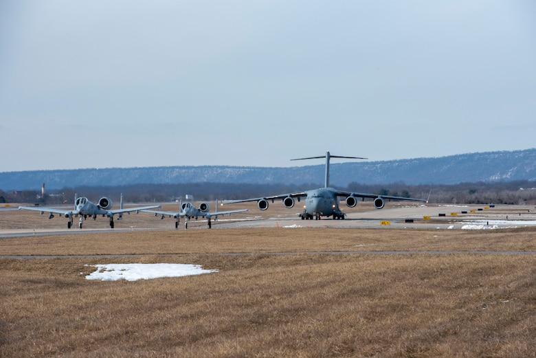 Two A-10 Thunderbolt II aircraft from the 104th Fighter Squadron of the 175th Wing, Maryland Air National Guard, and a C-17 Globemaster III with the 167th Airlift Squadron, 167th Airlift IWng, West Virginia Air National Guard, taxi to the runway at Shepherd Field, Martinsburg, West Virginia, Feb. 17, 2021, as part of an exercise to demonstrate Agile Combat Employment (ACE) capabilities.