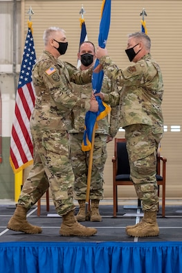 U.S. Army Brig. Gen. William Crane, the Adjutant General for the West Virginia National Guard, passes the flag representing the 2,100 members of the West Virginia Air National Guard to U.S. Air Force Brig. Gen. Ray Shepard during a change of command ceremony held at the 167th Airlift Wing, Shepherd Field, Martinsburg, West Virginia, March 7, 2021.