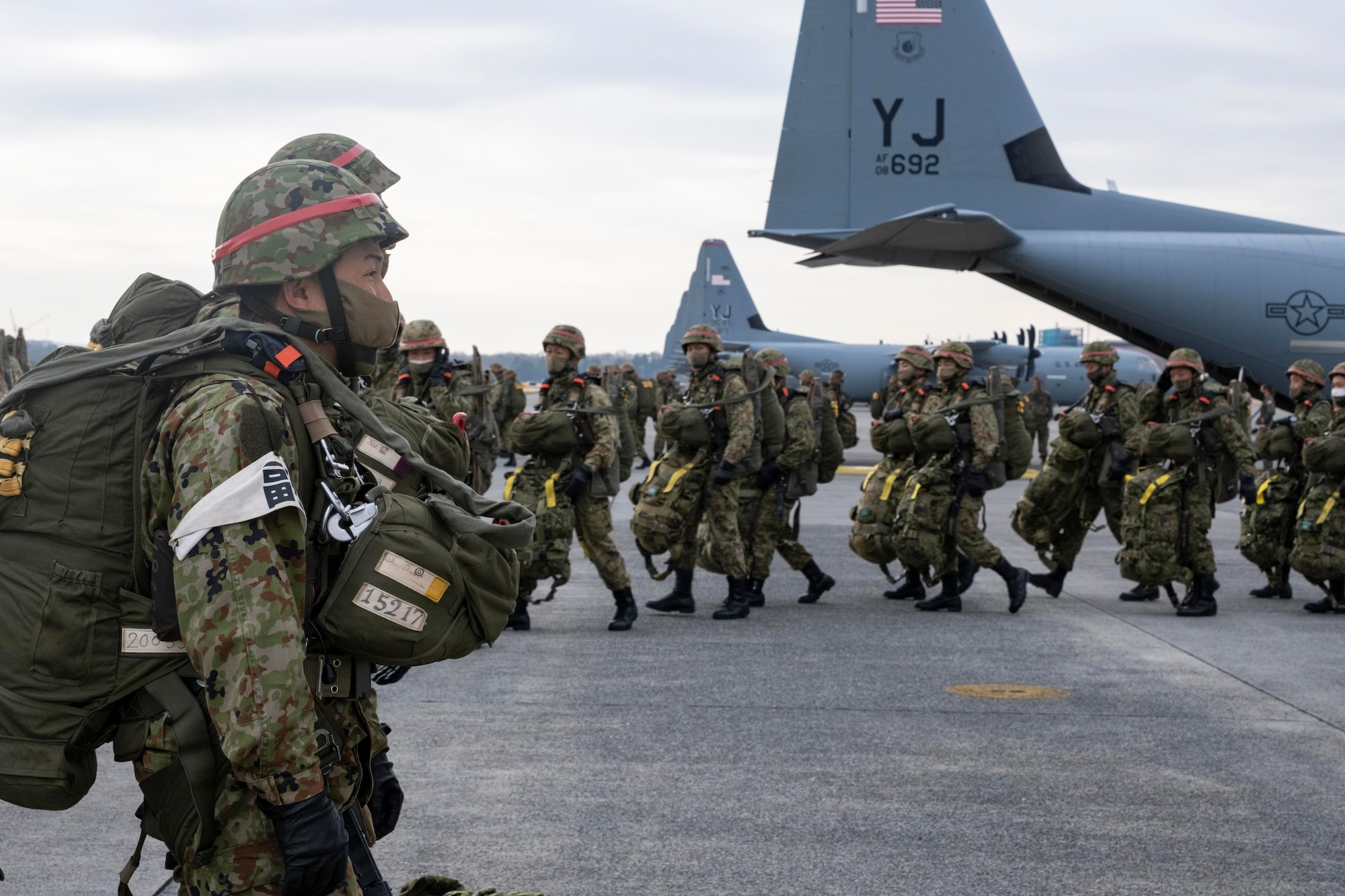 Japan Ground Self Defense Force paratroopers line up to load onto a C-130J Super Hercules, assigned to the 374th Airlift Wing, during exercise Airborne 21 at Yokota Air Base, Japan, March 9, 2021.