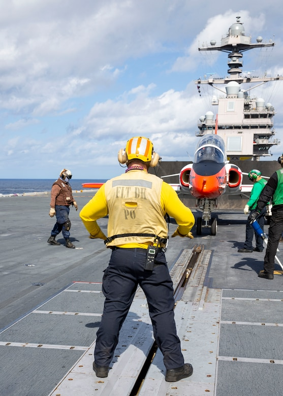 """210205-N-UF271-1028 ATLANTIC OCEAN (Feb. 5, 2021) Sailors assigned to USS Gerald R. Ford's (CVN 78) air department, prepare to launch Italian navy Ensign Erika Raballo, a student naval aviator assigned to the """"Tigers"""" of Training Squadron 9, in a T-45C Goshawk aircraft from Ford's flight deck Feb. 5, 2021. Carrier qualification is one of the final elements of the undergraduate strike pilot training curriculum under Chief of Naval Air Training. Ford is underway in the Atlantic Ocean conducting carrier qualifications. (U.S. Navy photo by Mass Communication Specialist Seaman Anton Wendler/Released)"""