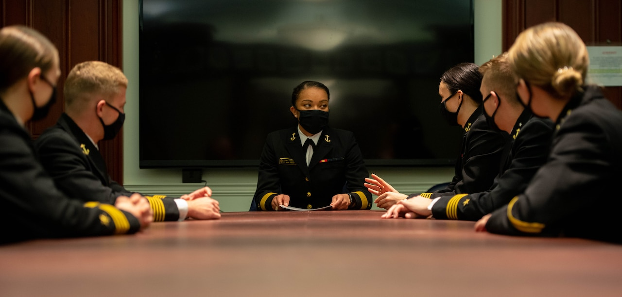 The Naval Academy's first black female brigade commander meets with other sailors.