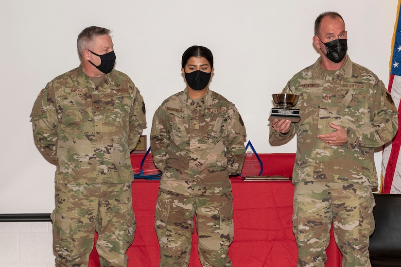 U.S. Air Force Brig. Gen. Ray Shepard, the Assistant Adjutant General- Air for West Virginia, left, and Command Chief Master Sgt. David Stevens, West Virginia Air National Guard Command Chief, right, present Airman 1st Class Pujaba Chudasama, with the James Kemp McClaughlin trophy during the 167th Airlift Wing's Outstanding Airman of the Year ceremony March 7, 2021.