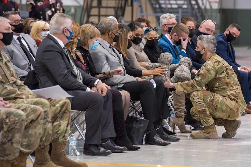 U.S. Air Force Master Sgt. Chris Taylor, chief of the 167th fire department presents London Brown with two teddy bears made from Staff Sgt. Logan Young's uniform during a memorial service held at the 167th Airlift Wing, Shepherd Field, Martinsburg, West Virginia, March 6, 2021. Brown was engaged to Young who died while fighting a fire in December.
