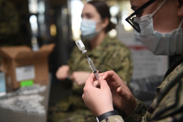 Hospital Corpsman Mazzy Dick, staff corpsman for Naval Medicine Readiness and Training Command, Portsmouth, fills syringes with Pfizer's COVID-19 vaccine to begin the vaccination process.