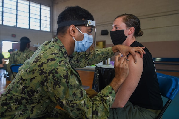 Hospital Corpsman 1st Class Sujit Rajendran, dental leading petty officer for Pre-Commissioning (PCU) John F. Kennedy (CVN 79), administers a Pfizer COVID-19 vaccine to Lt. j.g. Kelly Evertson, pilot for Helicopter Sea Combat (HSC) Squadron 11.