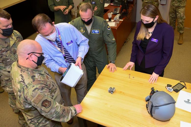 Airmen watch a demonstration of a 3D scanner.