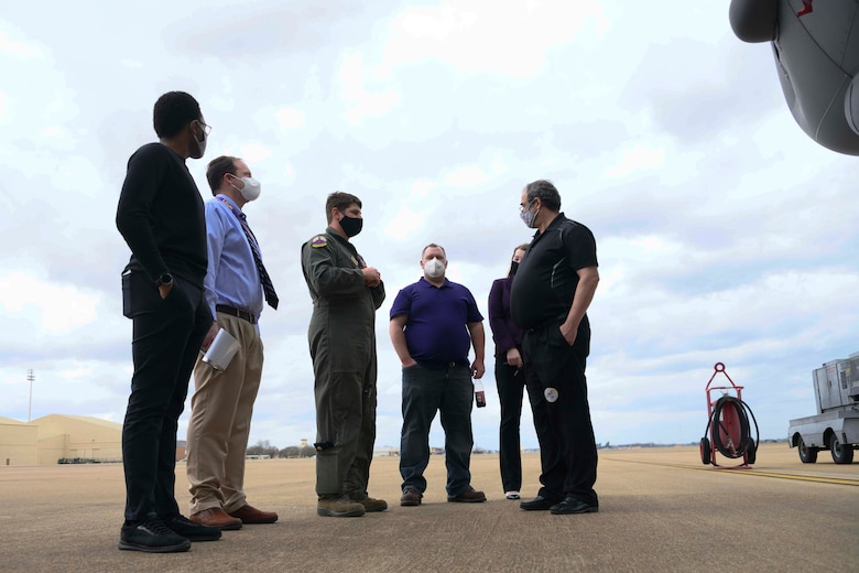 A group of people converse on the flight line at Barksdale Air Force Base.
