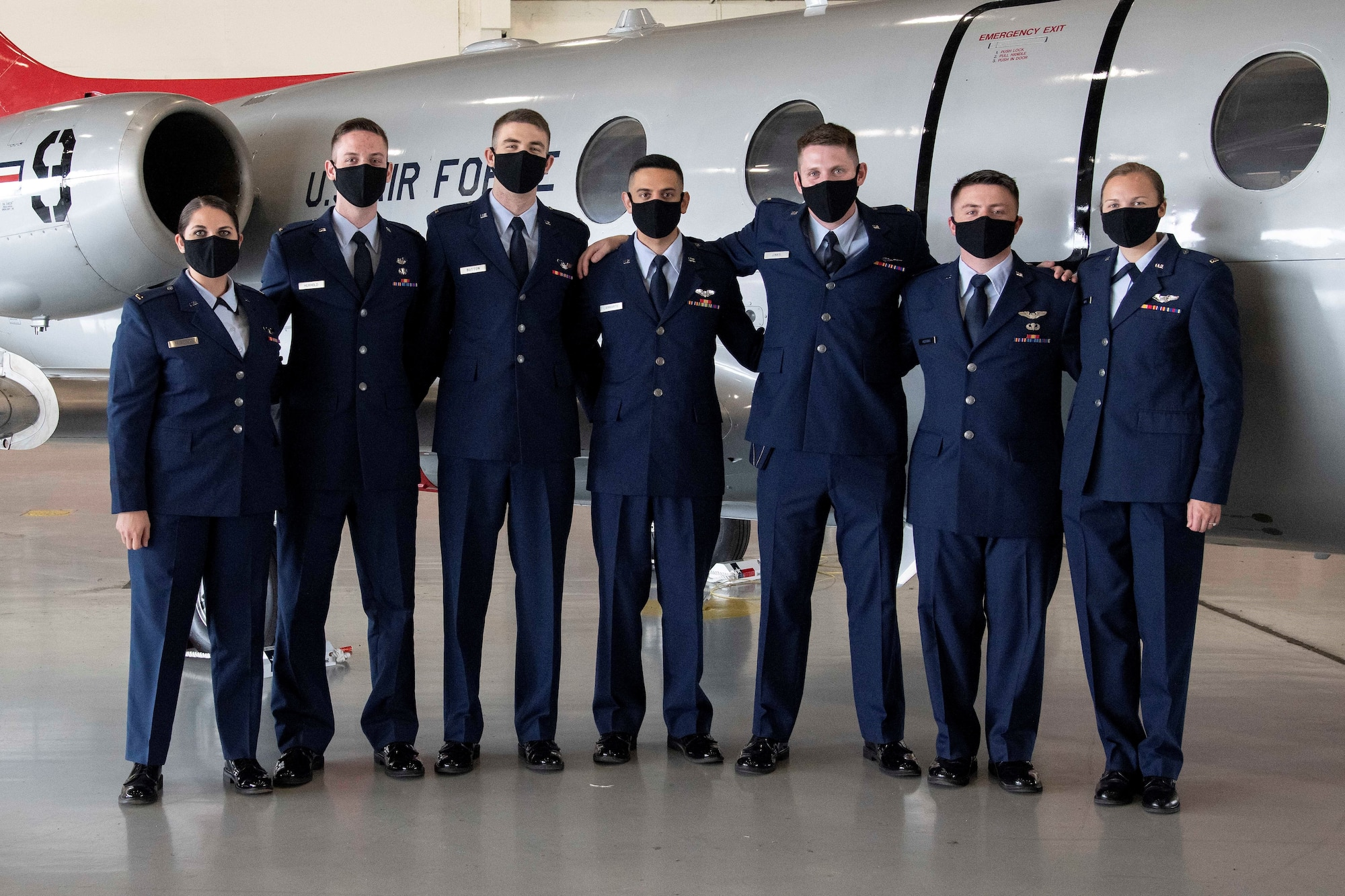 """Graduates from the first-ever """"Accelerated Path to Wings"""" class gather in front of a T-1 Jayhawk aircraft after receiving their pilot wings March 12, 2021 at Joint Base San Antonio-Randolph, Texas. Accelerated Path to Wings is part of Air Education and Training Command's pilot training transformation program, a two phase T-1 only pilot training tract. The 99th Flying Training Squadron is responsible for executing the seven month training mission that culminates with students earning their pilot wings."""