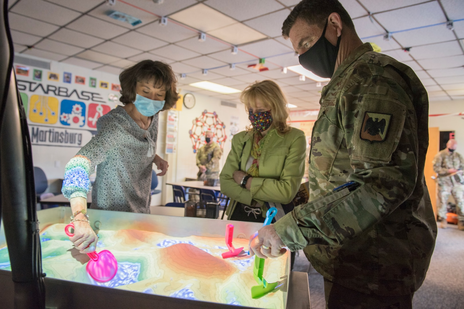 Sherra Triggs, left, director of STARBASE Martinsburg, speaks with U.S. Air Force Lt. Gen. Michael A. Loh, director, Air National Guard, and his wife Diane Loh, about teaching STARBASE curriculum through the COVID-19 pandemic, during their visit to the 167th Airlift Wing, West Virginia National Guard, at Shepherd Field Air National Guard Base in Martinsburg, West Virginia, March 9, 2021. During his visit, Loh received updates on the unit's current operations and response to the COVID-19 pandemic
