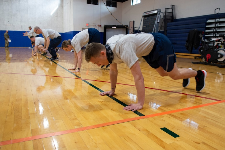 Senior Airman David Halbur, 434th Civil Engineer Squadron engineer assistant, and others from Grissom Air Reserve Base, Ind. perform modified burpees as part of physical fitness testing assessment, March 13, 2021. Airmen volunteered to test new components to the Air Force fitness assessment and gave their feedback as part of a pilot program here. (U.S. Air Force photo by Staff Sgt. Michael Hunsaker)
