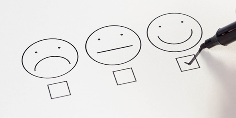 Drawing of 3 faces: an unhappy face, a neutral face and a happy face with filled check box under the happy face.