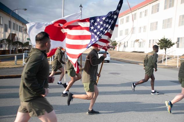 キャンプ富士の隊員や従業員など120名余りが3月11日、日米両国旗を掲げ列を組んで東日本大震災追悼のランを行いました