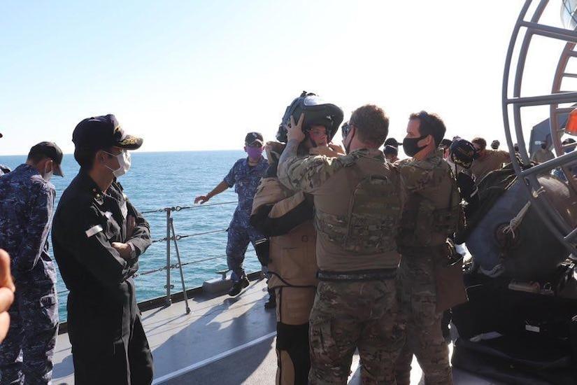 Sailors help a diver into his suit.