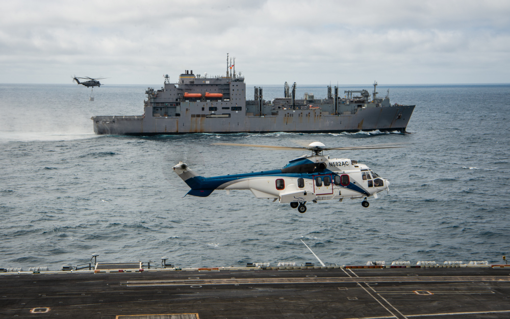 A civilian AS332 Super Puma, front, and a U.S. Marine Corps CH-53 Sea Stallion conduct the first a vertical replenishment-at-sea of an F-135 engine power module load simulator from the USNS Richard E. Byrd (T-AKE 4) to the Nimitz-class nuclear aircraft carrier USS Carl Vinson (CVN 70). The exercise uses mock weight measured to the same capacity as the F135 engine power module to verify the capability of supplying the parts necessary to support future joint strike fighter deployments. Vinson is currently underway in the Pacific Ocean conducting routine maritime operations. (U.S. Navy photo by Mass Communication Specialist 3rd Class Olympia O. McCoy/Released)