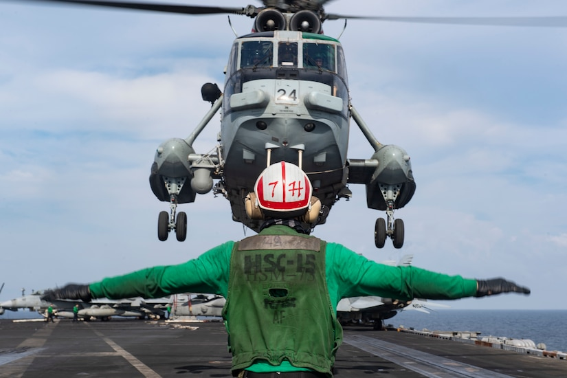 A sailor guides a helicopter as it lands on an aircraft carrier.