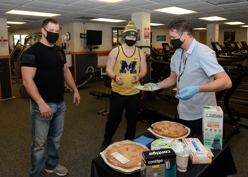 David Potter, left, and Schuyler Slone, center, receive their slices of pie from Dan Roberts, a recreation assistant and personal trainer with MWR in the Fitness Center March 12 during the first day of the annual Pi Day event.