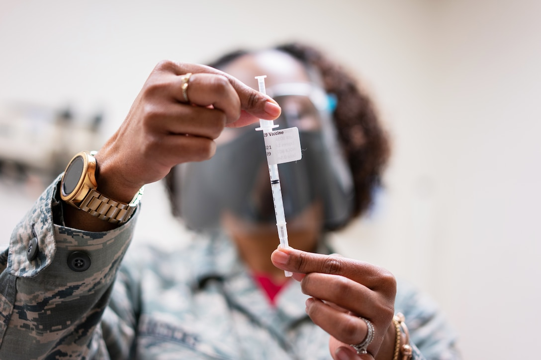 An airman wearing a face mask holds up a syringe to examine it.