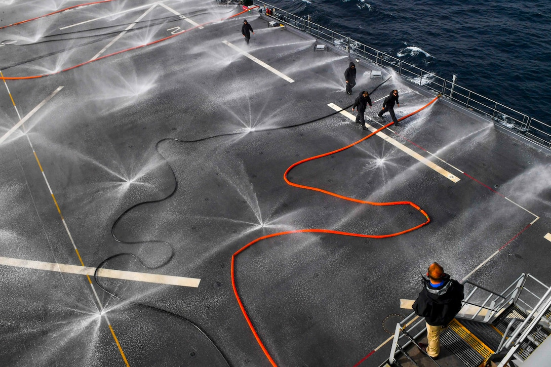 Sailors stand on the deck of a ship and watch sprinklers spray water.