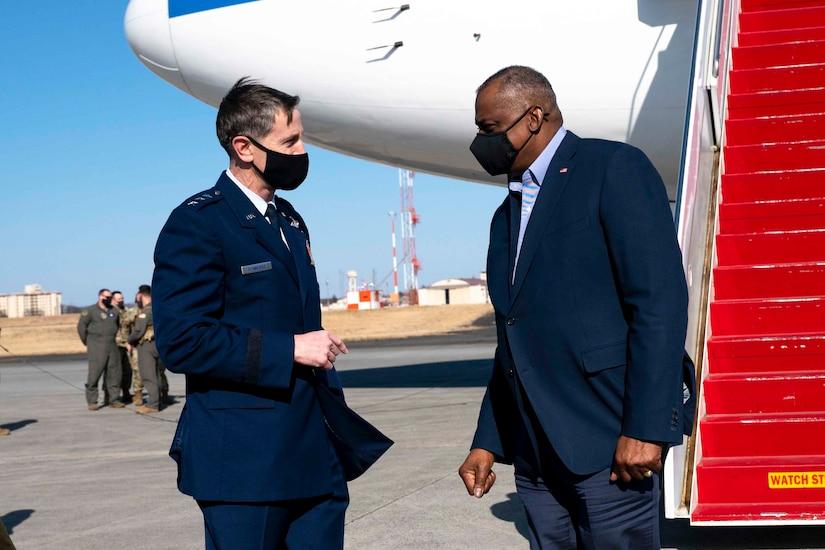 Secretary of Defense Lloyd J. Austin III stands facing an airman in front of a plane on a flightline.