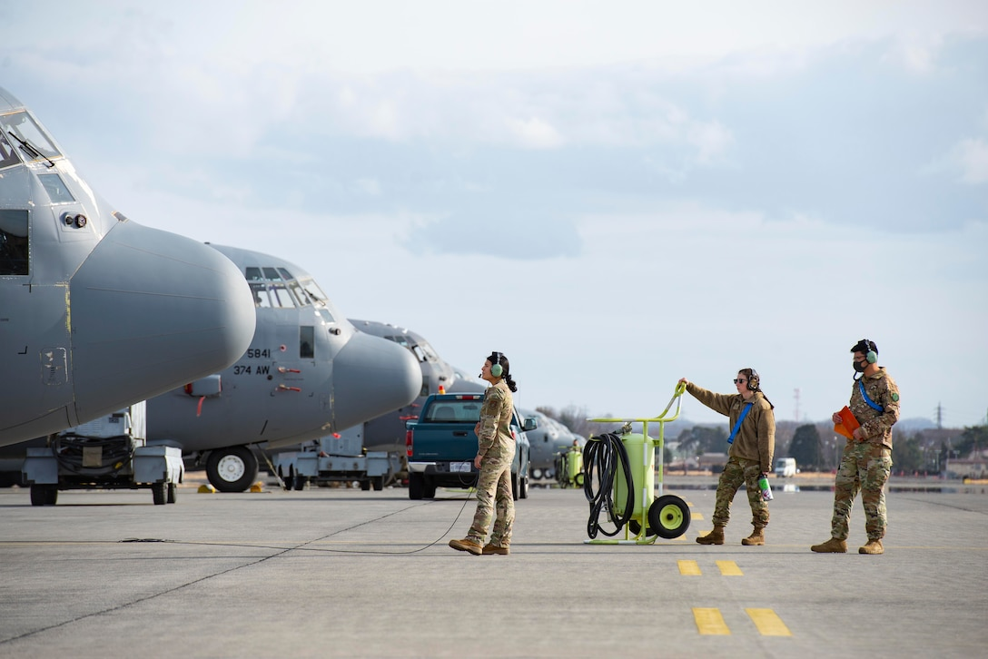 Maintainers and loadmasters watch an engine start up on a C-130J Super Hercules.