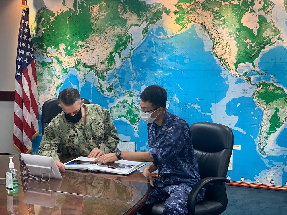 U.S. Navy Lt. Cmdr. Cory Eggers, left, replenishment officer with Commander, Logistics Group Western Pacific (COMLOG WESTPAC) and Japan Maritime Self-Defense Force Lt. Cmdr. Shuzo Homma discuss naval ships in the COMLOG WESTPAC conference room. (U.S. Navy photo by Lt. Teddy Haghverdi)