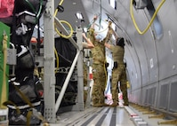 Airmen from the 433rd Aeromedical Evacuation Squadron route oxygen hoses and electrical extension cords aboard a KC-46A Pegasus March 10, 2021, at Joint Base San Antonio-Lackland, Texas. The medics were conducting initial qualification training on the new aircraft. (U.S. Air Force photo by Tech. Sgt. Iram Carmona)