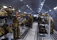 433rd Aeromedical Evacuation Squadron medics receive simulated patients onboard a KC-46A Pegasus during initial qualification training March 9, 2021, at Joint Base San Antonio-Lackland, Texas. During the training flights, the personnel simulated providing patient care to include responding to medical emergencies. (U.S. Air Force photo by Senior Airman Brittany Wich)