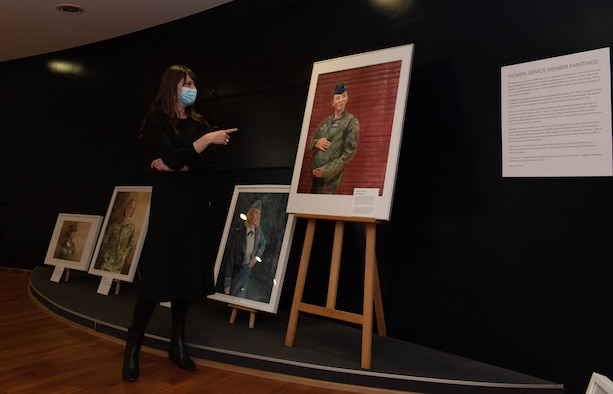 Woman kneels in front of painting