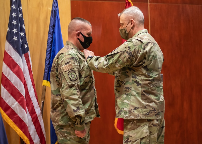 Utah Air National Guard Tech. Sgt. Erik Bornemeier, a medical technician assigned to the 151st Medical Group, Detachment 1, receives the Utah Cross from Maj. Gen. Michael J. Turley, adjutant general, March 15, 2021, at Roland R. Wright Air National Guard Base. The Utah Cross is the second-highest state award a Utah National Guard military member can receive.