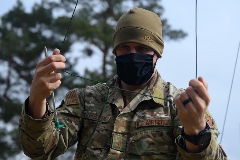 An Airman untangles a wire.
